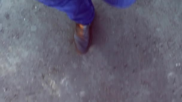 A man in jeans and black boots is walking on an asphalt road. Human legs top view.