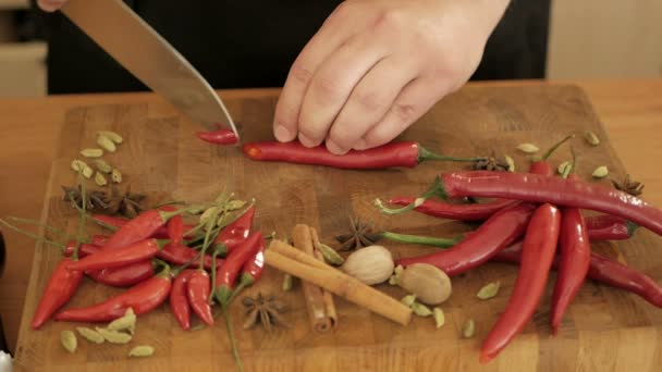 The cook slices hot chili peppers on the wooden board