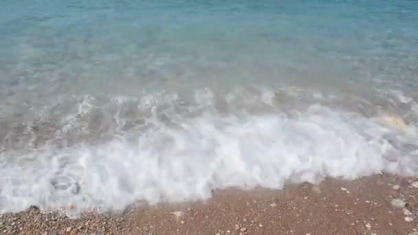 Grainy sand tropical beach, blue ocean sea wave washes the shore. Montenegro beach