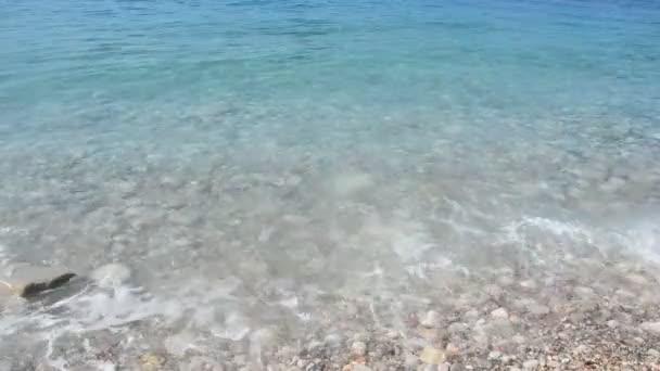 Zrnitý písek tropické pláže, modré moře mořská vlna omývá pobřeží. Pláž Černá Hora