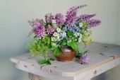 Still life with a bouquet of wild flowers in a clay vase on the table