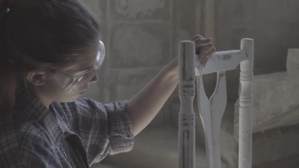 das Mädchen arbeitet in einer Tischlerei, poliert Möbel.