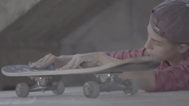 ein Mädchen in der Werkstatt poliert mit Schleifpapier Skateboard