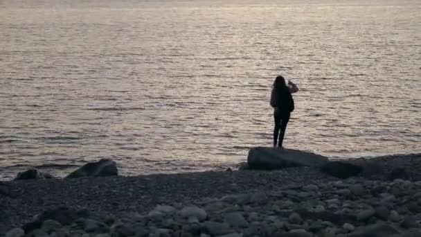 Young woman making selfie while standing on the beach with smartphone and headphones at sunset