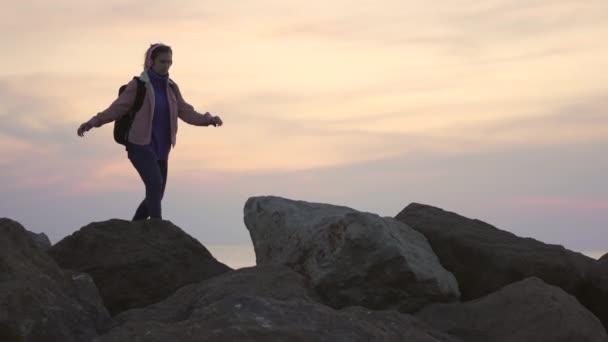 Fiatal lány utazó sétál a hegygerincen. Meredek hegy, gyönyörű kilátás nyílik az óceánra naplementekor
