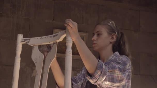 Ein junges Mädchen in seiner Werkstatt führt Schreinerarbeiten aus. Reparatur von antiken Möbeln