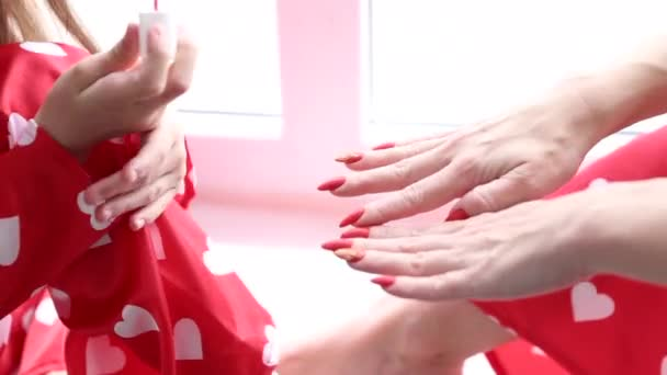 mother and daughter painting each other nails and toe nails
