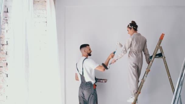 Frau steht auf einer Leiter, während ihr Mann die Wand bemalt