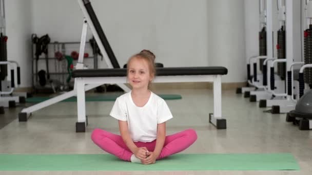 Little girl stretching and working on her splits