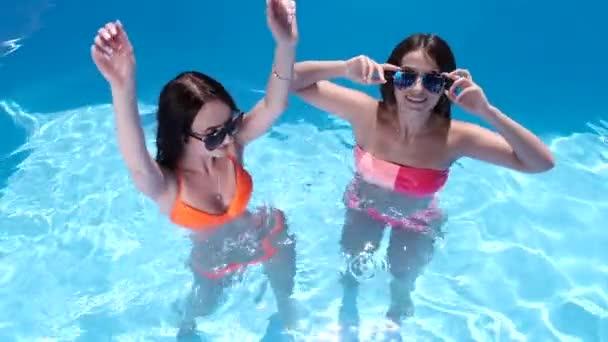 dvě děvčata tančí a baví se v bazénu