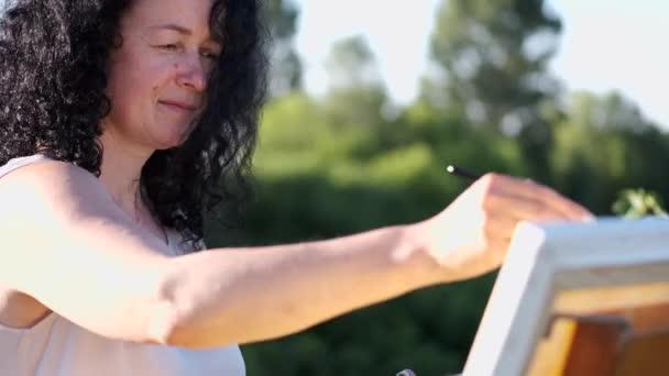 ženská umělkyně namalování barevného obrazu venku
