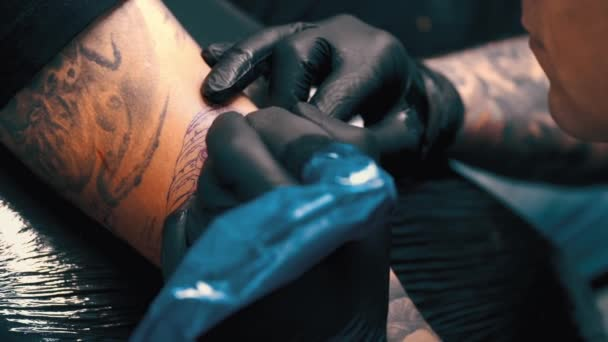 male tattoo artist tattooing a client