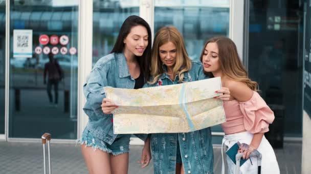 Děvčata se dívají na mapu blízko letiště