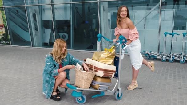 Lányok keres a térképen közelében repülőtér bőröndök