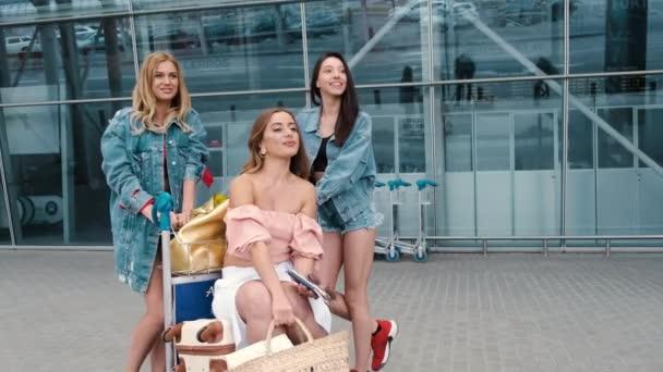 Děvčata se dívají na mapu blízko letiště s kufry