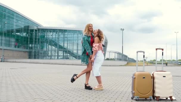Girls in full height posing for photo next to airport