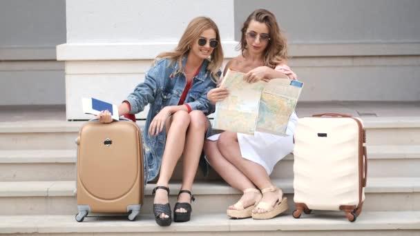 Dívky, které sedí na schodech a drží mapu se zavazadly