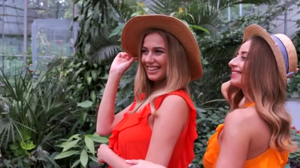 Portrait of girls with blonde hair in hats posing in botanic garden