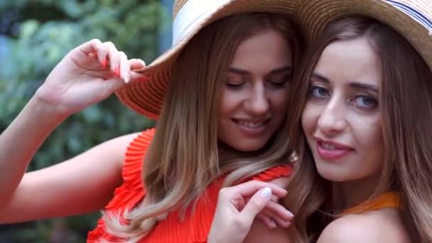 Portrait of girls with blonde hair in hats posing in botanic garden