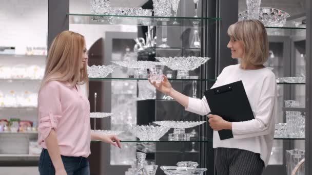 Žena si vybírá skleněné zboží s prodejním asistentem v obchodě s nádobím