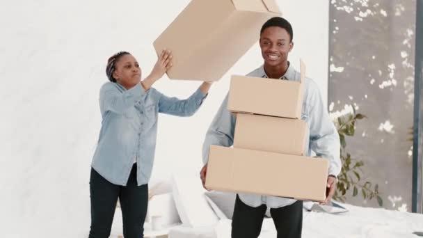 Afroamerikanisches Paar spielt in Wohnung mit Kisten