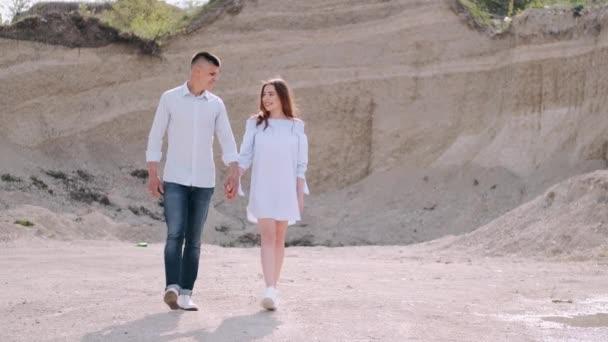 Muž a žena kráčí a drží se za ruce v kariéře