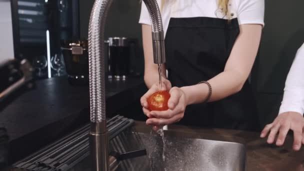 Frau wäscht Gemüse in Küche aus nächster Nähe