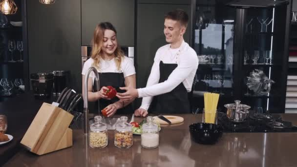Couple washing vegetables in kitchen close up