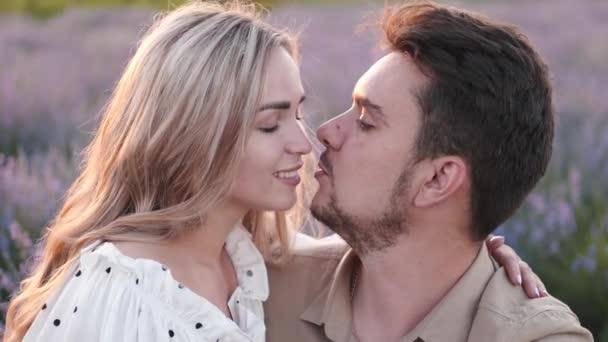 Liebevolle junge Paare küssen sich im Lavendelfeld und umarmen sich