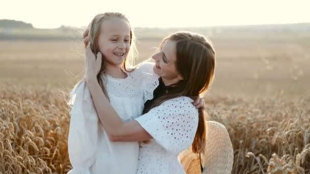 Mother and daughter hugging and having fun in wheat field