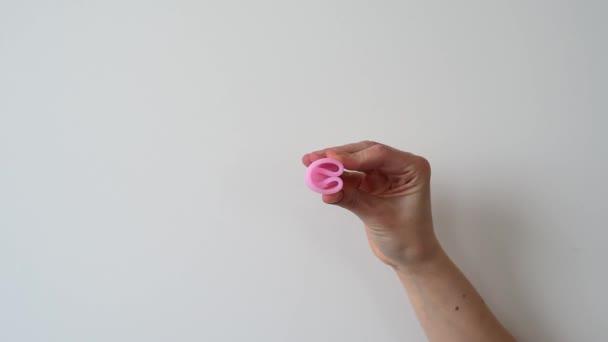 rosa Menstruationstasse in Frauenhand auf grauem Hintergrund mit weichem Licht