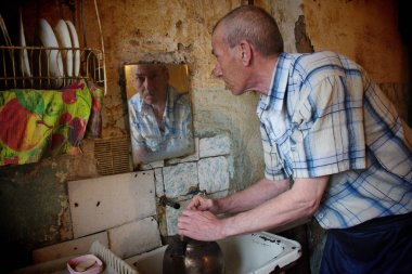 Barnaul,Russia-may 1, 2019. A man from a poor family pours water into the kettle in the kitchen