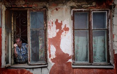 Barnaul,Russia-may 1, 2019. A man in a poor quarter looking out the window of an old house