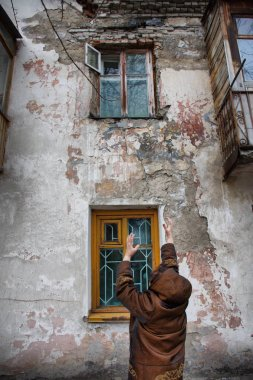 Barnaul,Russia-may 1, 2019. A woman stands near the Windows of an old house