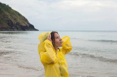 Portrait of woman on a rainy beach wearing a yellow raincoat.