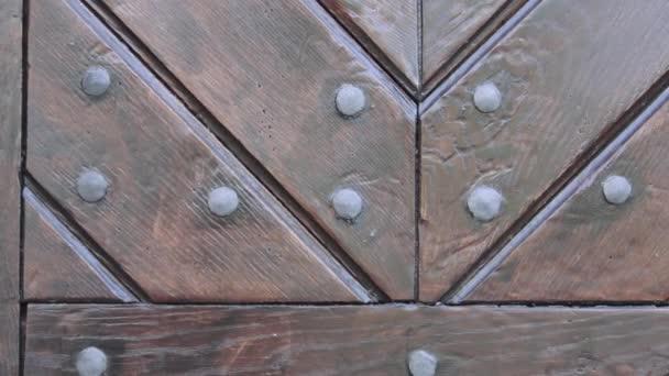 Rustikální hnědé dřevěné dveře texturu. Fragment dřevěné dveře s kovovými nýty. Textura starých dřevěných dveří