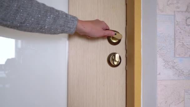 Dámská ruka otvírá a zavírá vnitřní dveře pomocí kliky.