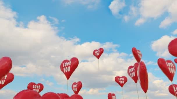 Červené balóny ws srdce tvaru mouchy vysoká modrá obloha