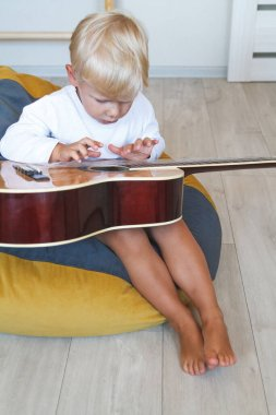 Little Boy learns to play acoustic guitar in his room