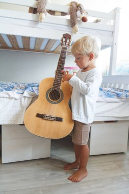 Boy learns to play acoustic guitar in his room