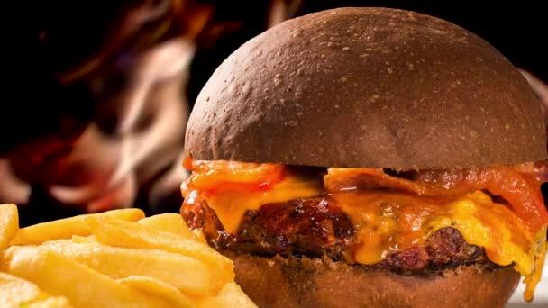 Lahodné hamburger se sýrem a slaninou na talíři s hranolky. Požár na pozadí rozostřené.