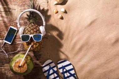 Ripe pineapple with sunglasses and headphones on beach sand.