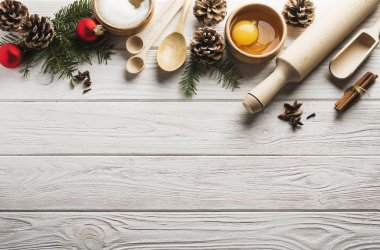 Christmas background with ingredients for holiday bakery on a white wooden background with copy space. Top view.