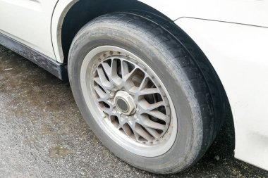 Car with worn bald tire unsafe and poses traffic accident risk