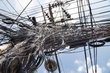 Messy entangled electricity, telecommunication wires, cables on poles in under-developed city