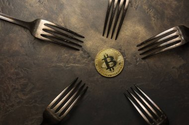golden bitcoin with silver forks around him