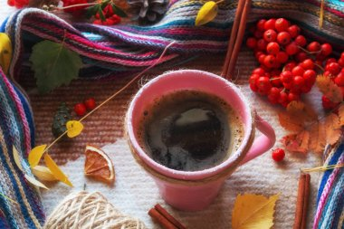 mug of hot coffee on a background of autumn colored leaves, a scarf and rowan berries. hello autumn concept