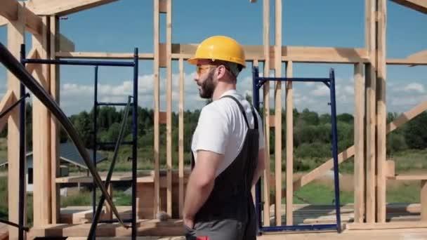 Der Mann ist Bauarbeiter auf dem Dach eines Fachwerkhauses.