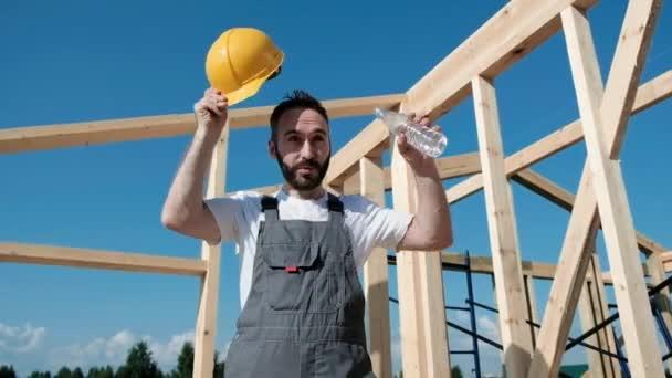 Mit gelbem Helm und grauen Overalls und weißem T-Shirt sitzt der Bauarbeiter auf dem Dachrand des Fachwerkhauses. er schüttet Wasser aus der Flasche auf den Kopf.