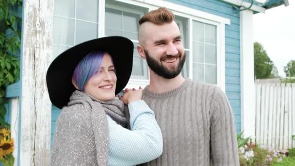 Mladá rodina, muž a žena na pozadí modré dřevěné vesnice dům